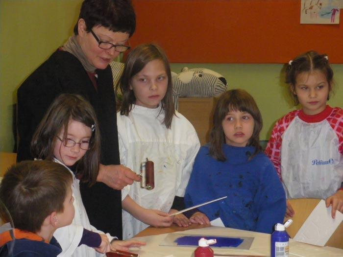 Bild 1: Frau Kook mit einigen Malschulkindern beim Erlernen einer Drucktechnik