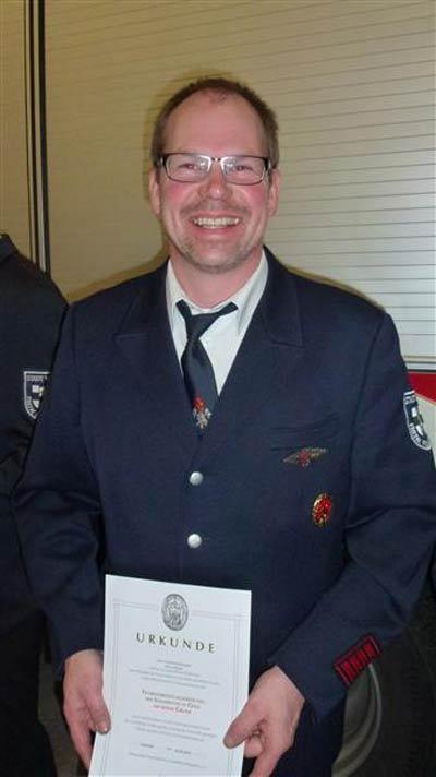 Klaus Meyer mit Urkunde und Feuerwehrzeichen Gold auf rotem Grund für 15 Teilnahmen an den Leistungswettkämpfen