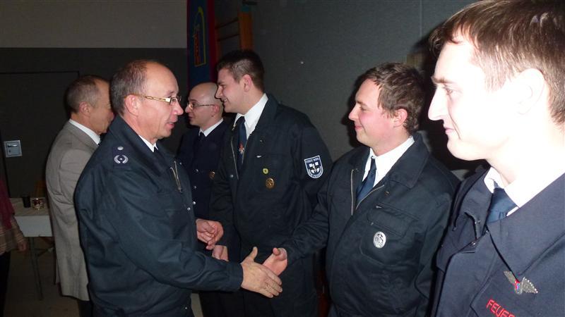 Stellvertretender Wehrführer Michael Goebel gratuliert Marc Poulet und Bürgermeister Michael Grosmann Hans Funk zur Beförderung.