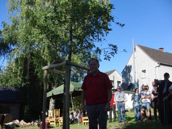 Aus Anlass des 40-jährigen Jubiläums pflanzen Westönner Schützen und Müscheder Musiker einen Baum in der Ortsmitte von Müschede